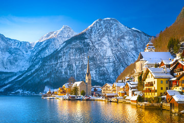 Classic postcard view of famous Hallstatt lakeside town in the Alps with traditional passenger ship...