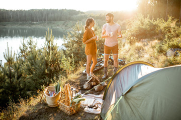 Tuinposter Kamperen Young couple standing at the campsite, talking and enjoying hot drinks while traveling in the mountains near the lake on the sunset