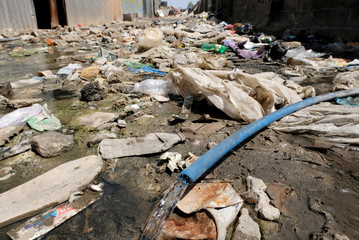 Water flows from a broken water pipe among the garbage at a displaced camp in Benghazi