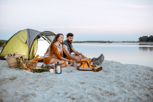 Young and cheerful couple sitting at the fireplace, cooking sausages, having a picnic at the campsite on the beach in the evening
