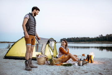 Tuinposter Kamperen Man and woman at the campsite on the beach, man carrying a bucket with fresh caught fish, woman cooking sausages on the fireplace