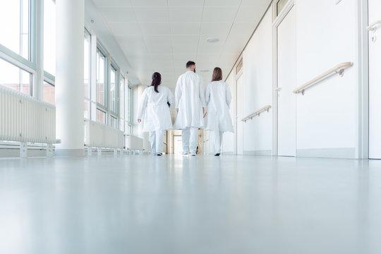 Three doctors walking down a corridor in hospital