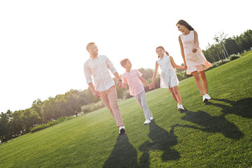 Spending weekend with family. Full length of happy and young family of four holding hands, smiling and walking outdoors in the nature
