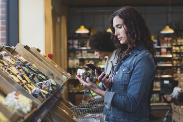 Young adult female using self scan in a grocery store