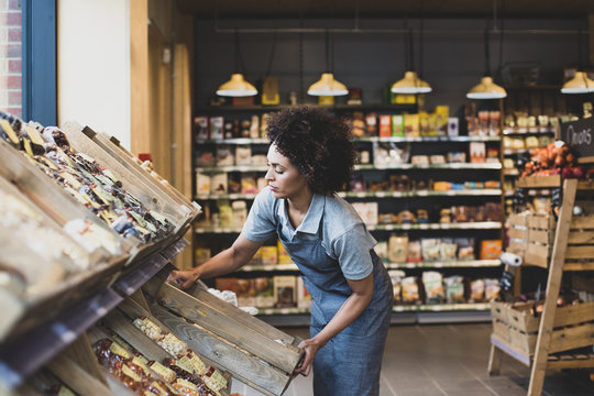 Small business owner of a food market stocking shelves
