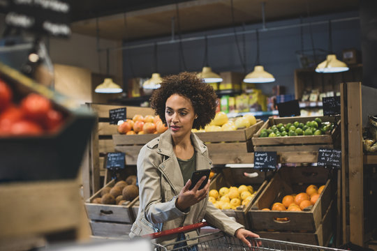 African American female late night grocery shopping and using smartphone