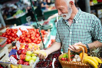 Handsome senior man shopping for fresh fruit and vegetable in a market