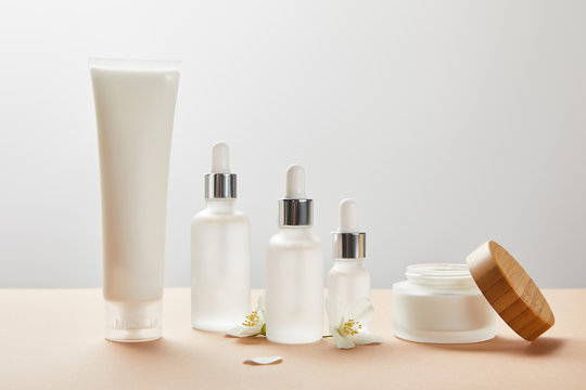 cream tube, cosmetic glass bottles, open jar with cream and few jasmine flowers on beige