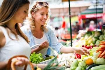 Young happy women shopping vegetables and fruits on the market Wall mural