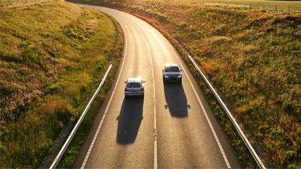 two cars traffic on uk motorway sunset view