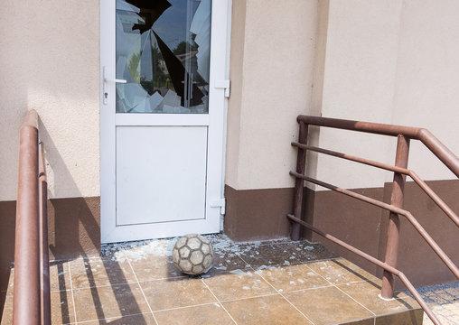 A football or soccer ball broke the window near football training area. Close-up, selective focus.