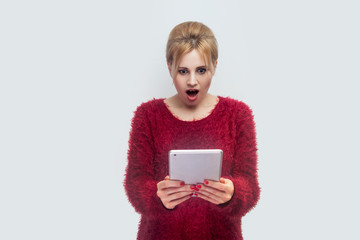 No way! Portrait of beautiful unbelievable young woman in red blouse standing and watching suprised video on her tablet with shocked face. Indoor, isolated, studio shot, grey background
