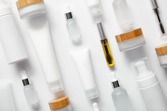 flat lay of cream tubes with hand cream, mascara bottles, cosmetic glass bottles, cosmetic dispensers and jars on white