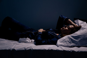 Sad alone woman lying the bed. Insomnia concept