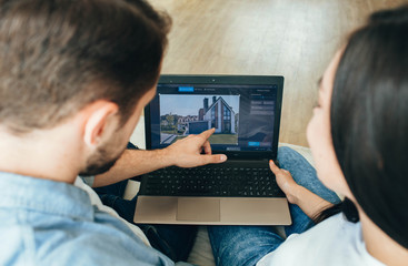 Fototapeta couple choosing new house using laptop. Scrolling the Internet in search of new estate