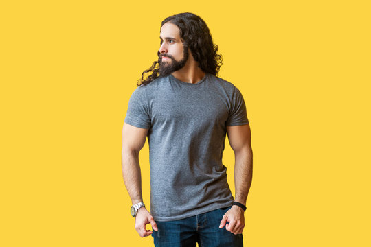 Portrait of brutal handsome bearded young man model with long curly hair in grey tshirt standing and looking away with serious proud face. indoor studio shot isolated on yellow background.