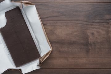 Top view of unwrapped dark chocolate bar. Flat lay image of bitten dark chocolate on brown table. Photo of nibbled unwrapped chocolate bar on dark brown wooden background with copy space.
