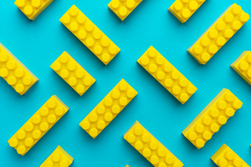 Top view of plastic blocks background. Flat lay image of toy background made with yellow building blocks from child constructor. Bright yellow plastic building blocks on torquoise blue background.