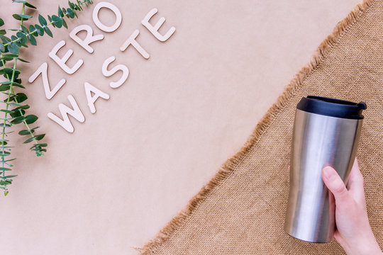 Reusable sustainable metal thermal coffee cup isolated on brown craft fabric background. Refuse, reduce, recycle and zero waste concept. Ecology, cut plastic footprint.