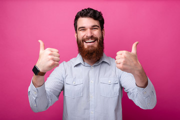 Cheerful bearded man in casual showing thumbs up gesture Wall mural