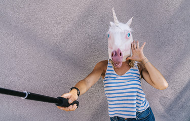 Freaky young woman in unicorn mask stands on a gray wall and use selfie stick to taking picture.