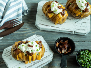Fototapete - baked potato stuffed with cheese, bacon and sour cream, loaded hasselback potatoes