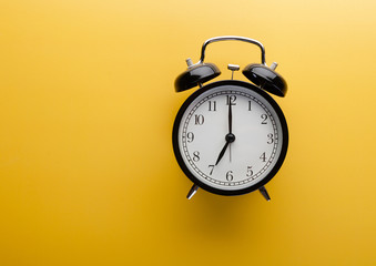 Alarm clock on yellow background top view. Concept of time. Wall mural