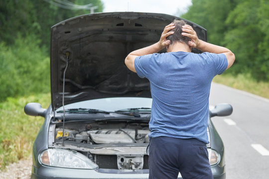 Middle-aged worried man stands with his hands on the head near his broken car with raised hood on the rural road
