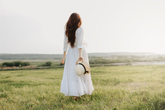 Beautiful carefree long hair girl in white clothes and straw hat enjoys life in nature field at sunset. Sensitivity to nature concept