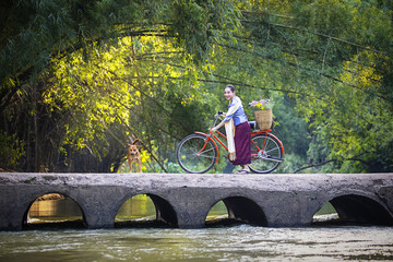 Asian beautiful women wear traditional clothing with bicycles on cement bridges, women and bikes and rivers.