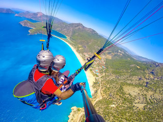 Extreme sport. Landscape . Paragliding in the sky. Paraglider tandem flying over the sea with blue water and mountains in bright sunny day. Aerial view of paraglider and Blue Lagoon in Oludeniz, Turke