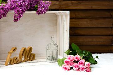 Kiste aus weissem Holz mit Flieder, Schild hello, einem Käfig und rosafarbenen Rosen vor einer Holzwand