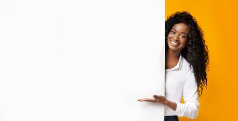 Fototapeta African-american man pointing at white blank board obraz