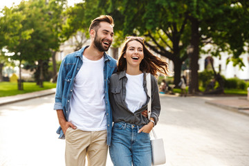 Beautiful young couple in love walking outdoors at the city street