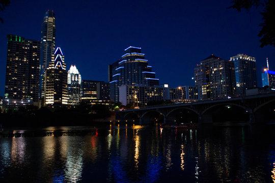 Austin skyline over Colorado river at night, Texas.