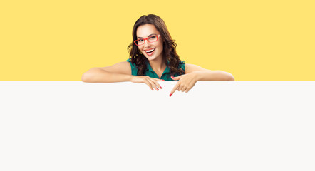 Happy smiling beautiful young woman in green clothing and red glasses, pointing blank white bill board or copy space empty place for ad slogan or sign text, over yellow color background Wall mural