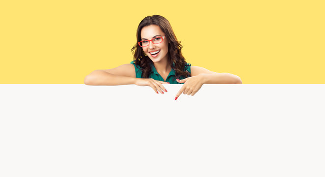 Happy smiling beautiful young woman in green clothing and red glasses, pointing blank white bill board or copy space empty place for ad slogan or sign text, over yellow color background