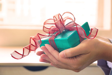 Woman give green gift box with background warm light from window.