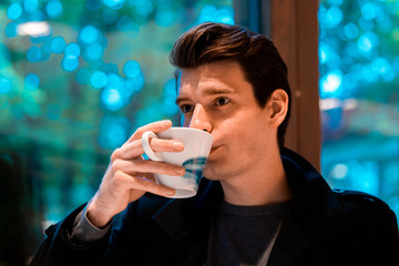 Handsome man drinking tea or coffee on rainy day and looking through the window