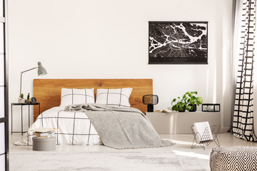 Copy space on white wall with black map in modern bedroom with king size bed with wooden headboard
