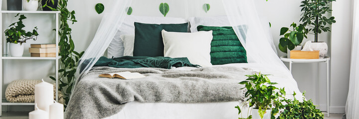Panoramic view of white and green bedroom with king size bed with emerald pillows and grey duvet Wall mural