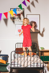 Happy girl jumping on her bed in white retro bedroom
