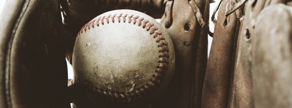 Baseball banner shows old rugged ball in mitt close up for sport gear.