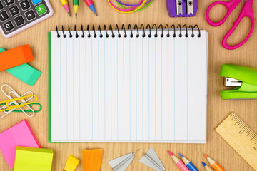 Blank, lined, coil notebook with school supplies frame against a wood desk background. Back to school concept. Copy space.