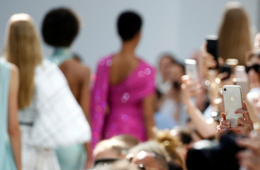 Guests take pictures with their mobile phones as models present creations by designer Alexandre Vauthier as part of his Haute Couture Fall/Winter 2019/20 collection show in Paris