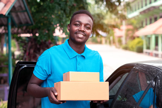 African man carrying package from delivery car