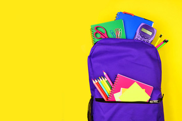 Purple backpack full of school supplies against a bright yellow background. Close up, top view with...