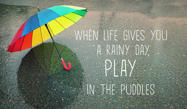 when life gives you a rainy day, play in the puddles - inspiration quote on autumn abstract blurred defocused background. rainbow umbrella in puddle, rainy weather season. soft selective focus