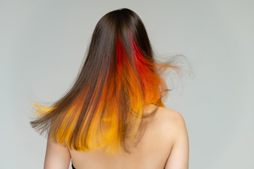 A close-up portrait photo of a fashionable hairstyle red-yellow in studio on a white background. The pretty brunette model with beautiful make-up has beautiful flowing colorful hair.
