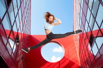Fit woman jumping on urban red background - Image